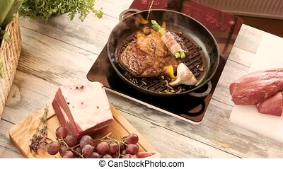 Cooking flambe steak. Tongs holding meat on pan. Hot and...