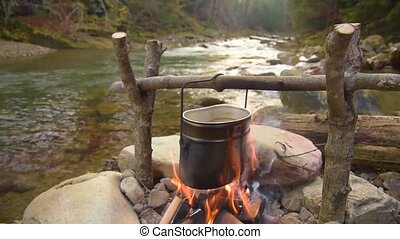 Cooking food in pot over campfire - Cooking on bonfire....