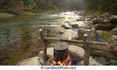 Cooking food in pot over campfire