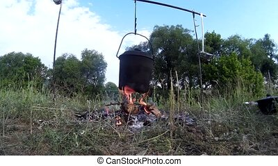 Cooking food on the campfire on river bank