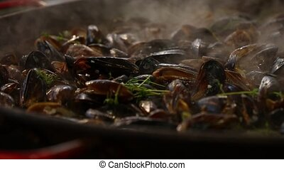 Cooking fresh steamed mussels at big frying pan