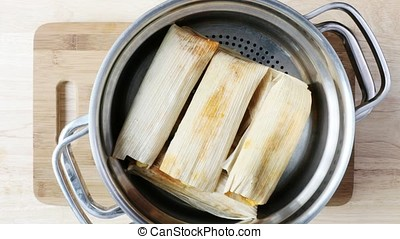 Cooking Fresh Tamales - Removing steamer full of tamales to...