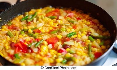 Cooking frozen vegetables in a pan close-up Mexican blend