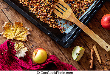 Cooking granola with apple and spices on a wooden table