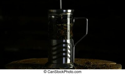 cooking green tea in french press in a glass teapot on a dark background. slow motion