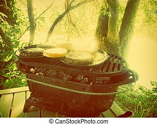 Cooking hamburgers burgers on grill barbecue in the woods forest camp camping food