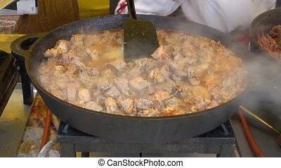 cooking hot meat stew in metal pan