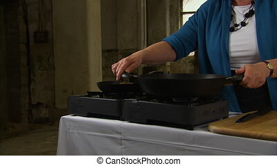 Cooking in a black steel pan - A steady medium shot of a...