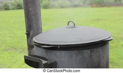 Cooking in a cauldron outside on a wood stove , steam from under the lid