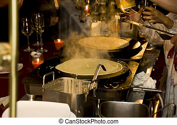 Busy crepe kitchen with two crepes ready.