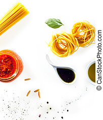 Scattered fresh ingredients on a white background for cooking Italian pasta with tomato paste, soy sauce, fresh basil, olive oil and uncooked spaghetti and fettucini