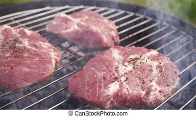 Cooking juicy raw meat steaks on the bbq grill in slow...