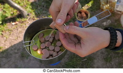 Cooking lunch in the wild - Young caucasian man cooking...