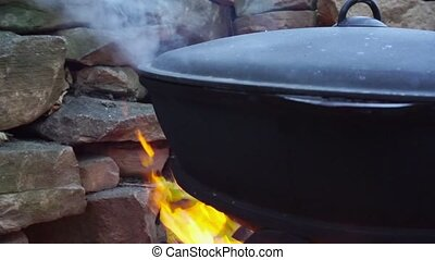 Cooking meat on a fire in cast-iron cauldron.