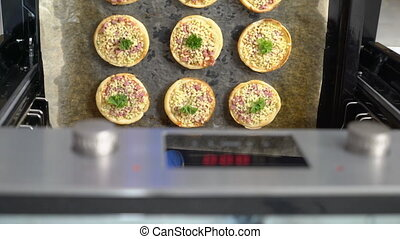 Cooking mini pizza topped with mozzarella cheese and ham in...