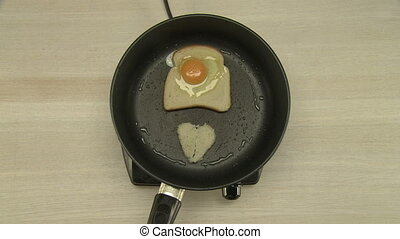 Cooking of breakfast with fried egg and toast