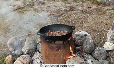 Cooking of meat in cauldron outdoors