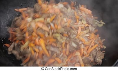 Cooking of pilaff with lamb, carrots and spices onions in a cauldron on a wood stove
