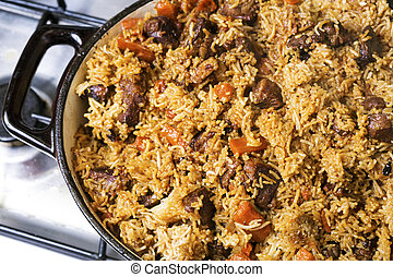 step-by-step process of cooking pilaf in a cast iron cauldron.