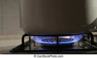 Cooking on gas stove, burner closeup, sliding camera