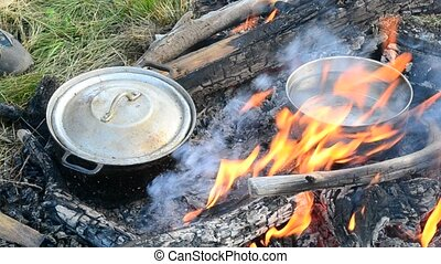 Cooking on open fire with wooden logs. Two pots standing in...