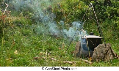 Cooking outdoor food in tourist pot at bonfire. Process preparing camping food on burning fire while hiking to wild nature