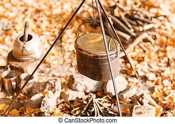 Cooking over a campfire in a cast iron pot. Cast iron pot...