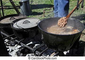 Cooking Over A Fire - Cast iron pots with lids cooking beans...