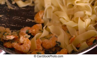 Cooking pasta with shrimps in a creamy garlic sauce. Mixing...