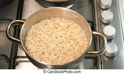 Cooking pearl-barley porridge on the stove