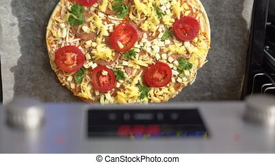 Cooking pizza topped with salami tomatoes mozzarella cheese...