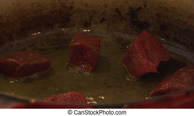 Cooking pork cubes in hot oil - A steady shot of pork being...