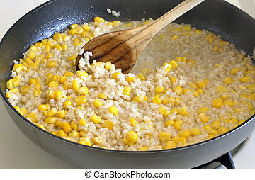 Cooking rice and corn - Rice and corn kernels cooking in a...