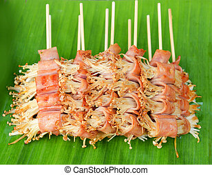 Cooking roll bacon wrapped enoki mushrooms for grilled on banana leaf delicious in street food