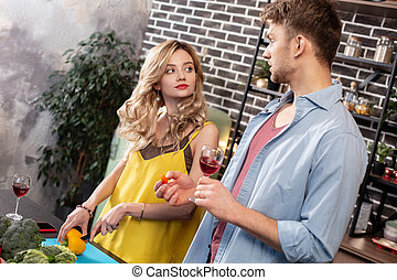 Curly blonde woman looking at her boyfriend while cooking salad