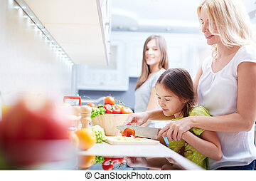 Cooking salad - Portrait of happy mother and two daughters ...