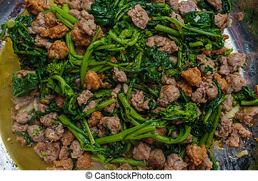 Cooking Italian spicy sausage and broccoli rabe in pot on kitchen stove