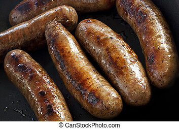 Cooking Sausages - Cooking sausages in a fry pan. Overhead...