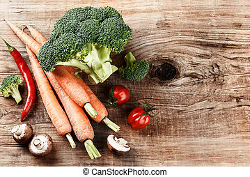 Cooking setting with fresh organic vegetables on old wood background