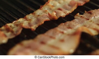 Cooking Slices of Bacon on a Grill Close-up