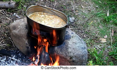 Cooking soup on a fire pot. Summer camping in forest.