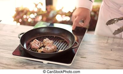 Cooking steaks in pan. Chef preparing meat.