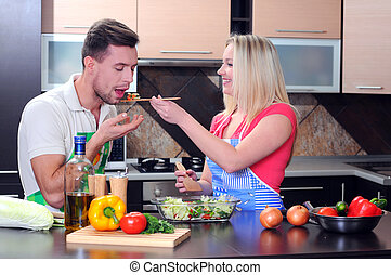Cooking - Young couple cooking - man and woman in their...