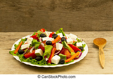 cooking summer Greek salad on wooden background