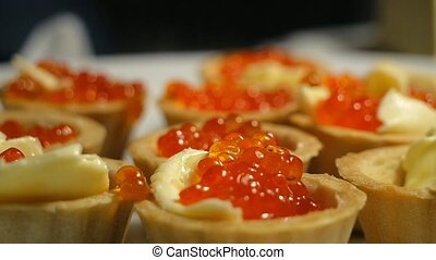 Cooking tartlets with red caviar and butter. Making tarts