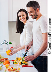 Cooking together is fun. Beautiful young loving couple cooking together while standing in the kitchen