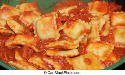 Cooking Tomato Sauce with Ravioli - Person simmering tomato...