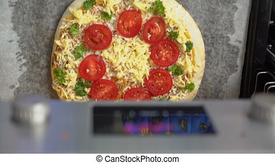 Cooking traditional italian pizza in the oven closeup top...