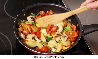 Cooking vegetable mixture with mushrooms in a pan on an...