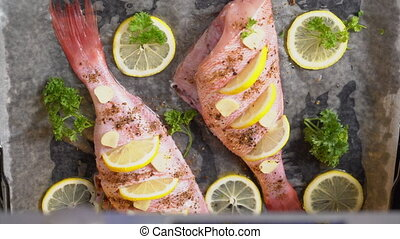 Cooking whole roasted fish with lemon and herbs baked in the...